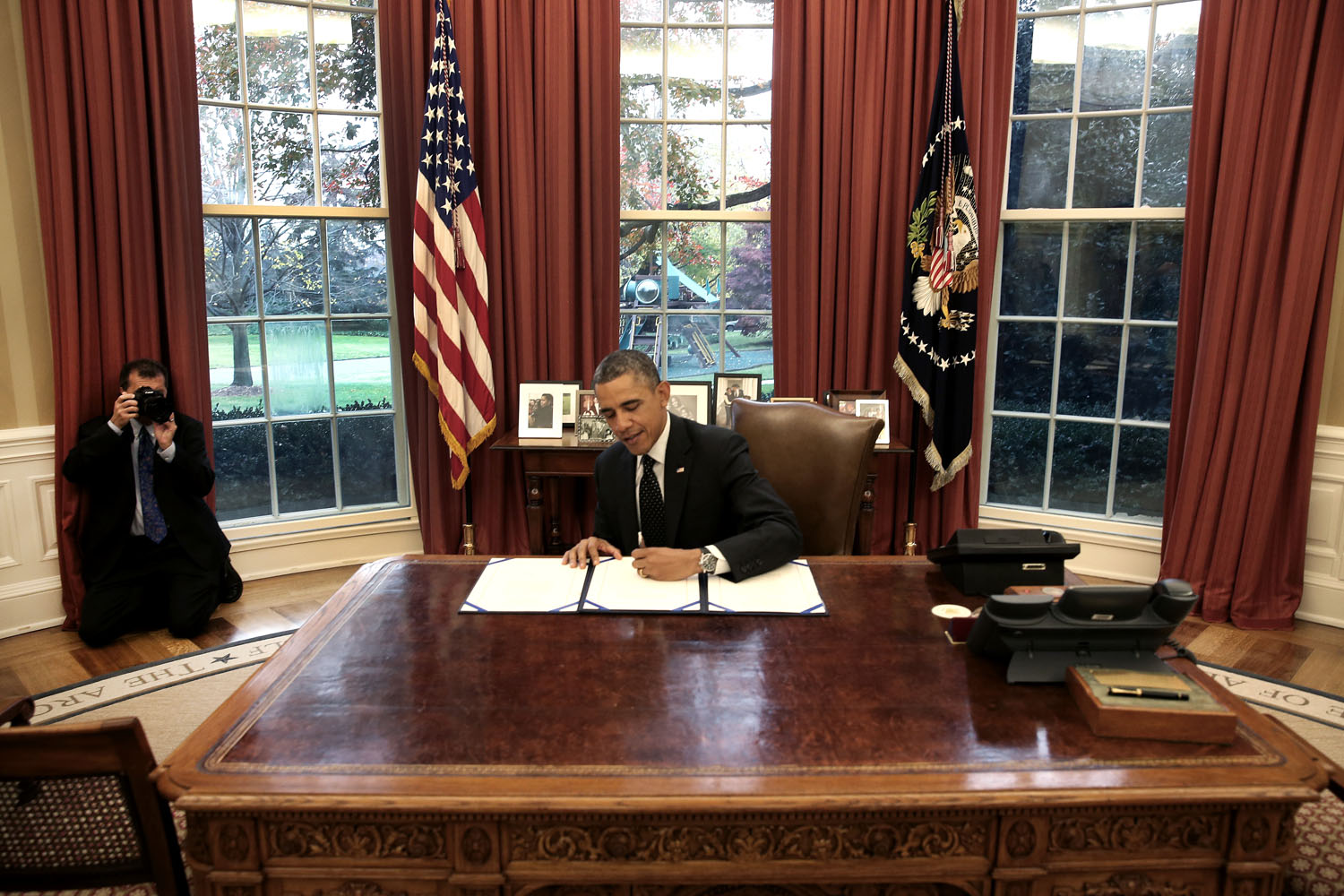 President Obama signs a bill as White House photographer Pete Souza takes pictures behind him in the Oval Office at the White House, on November 21, 2013.