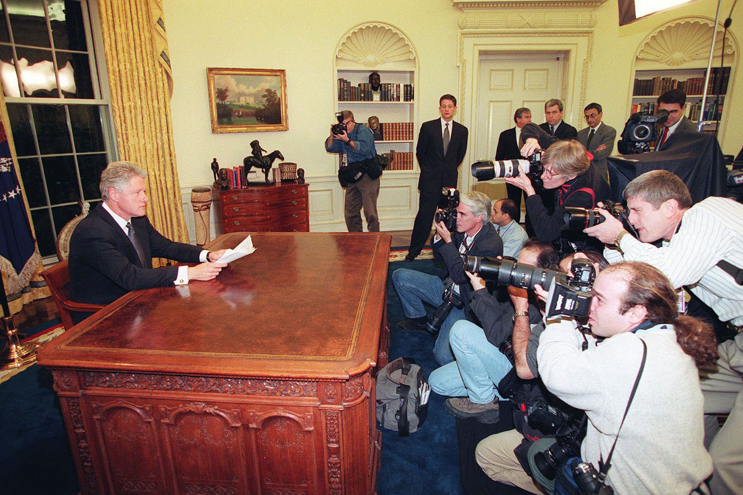 Photographers take pictures of President Bill Clinton as he prepares to address the nation from the White House on December 16, 1998.