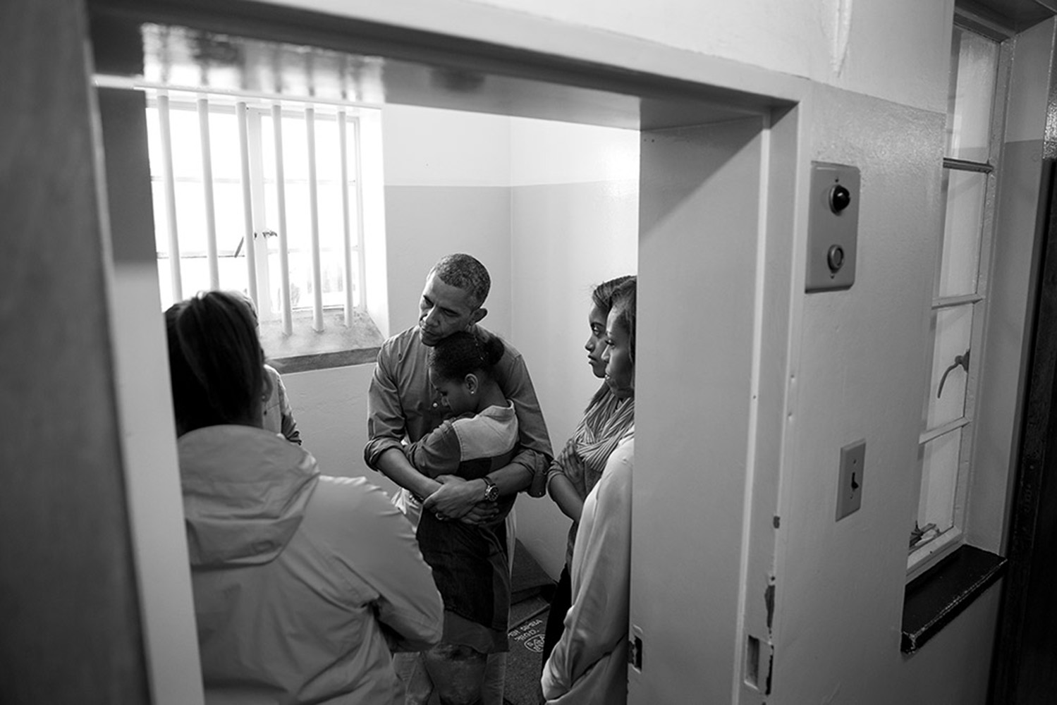 June 30, 2013. In this photo provided by the White House, President Barack Obama and First Lady Michelle Obama, along with daughters Sasha and Malia, stand in former South African President Nelson Mandela's cell as they listen to former prisoner Ahmed Kathrada during their tour of Robben Island Prison on Robben Island in Cape Town, South Africa.