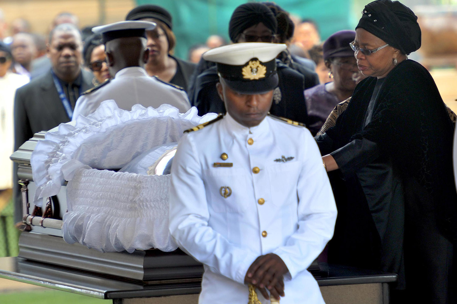 Dec. 11, 2013. This photo provided by the Government Communication and Information System of South Africa shows Nelson Mandela's widow Graca Machel pays her respects to former South African President Nelson Mandela during the lying in state at the Union Buildings in Pretoria, South Africa.