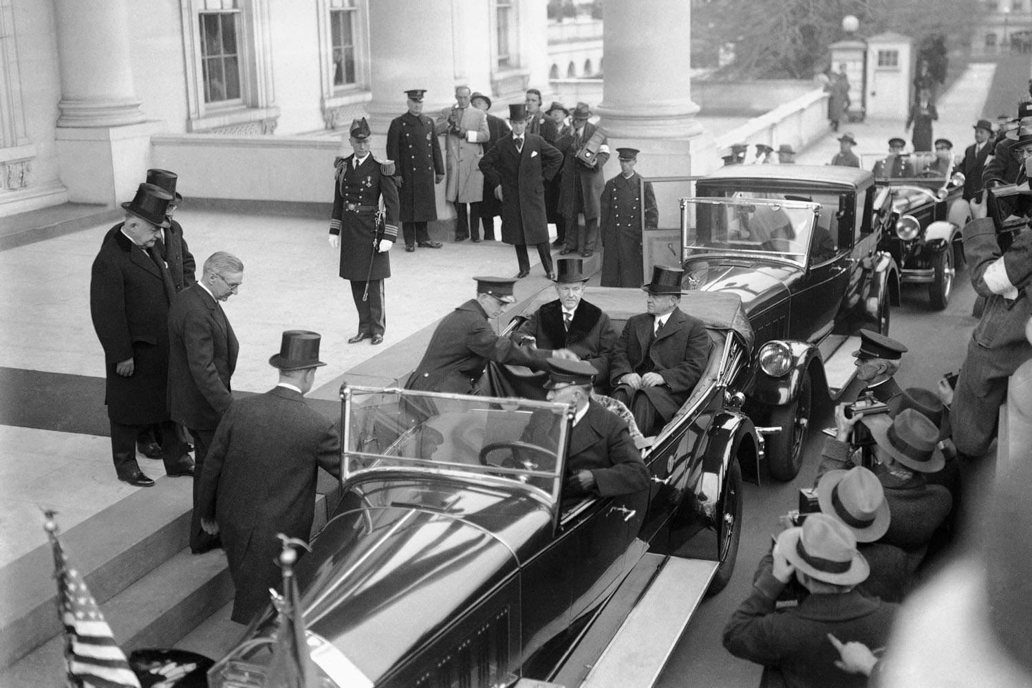 President Calvin Coolidge and President-elect Herbert Hoover, seated in car, depart the White House for Hoover's inauguration, March 4, 1929.