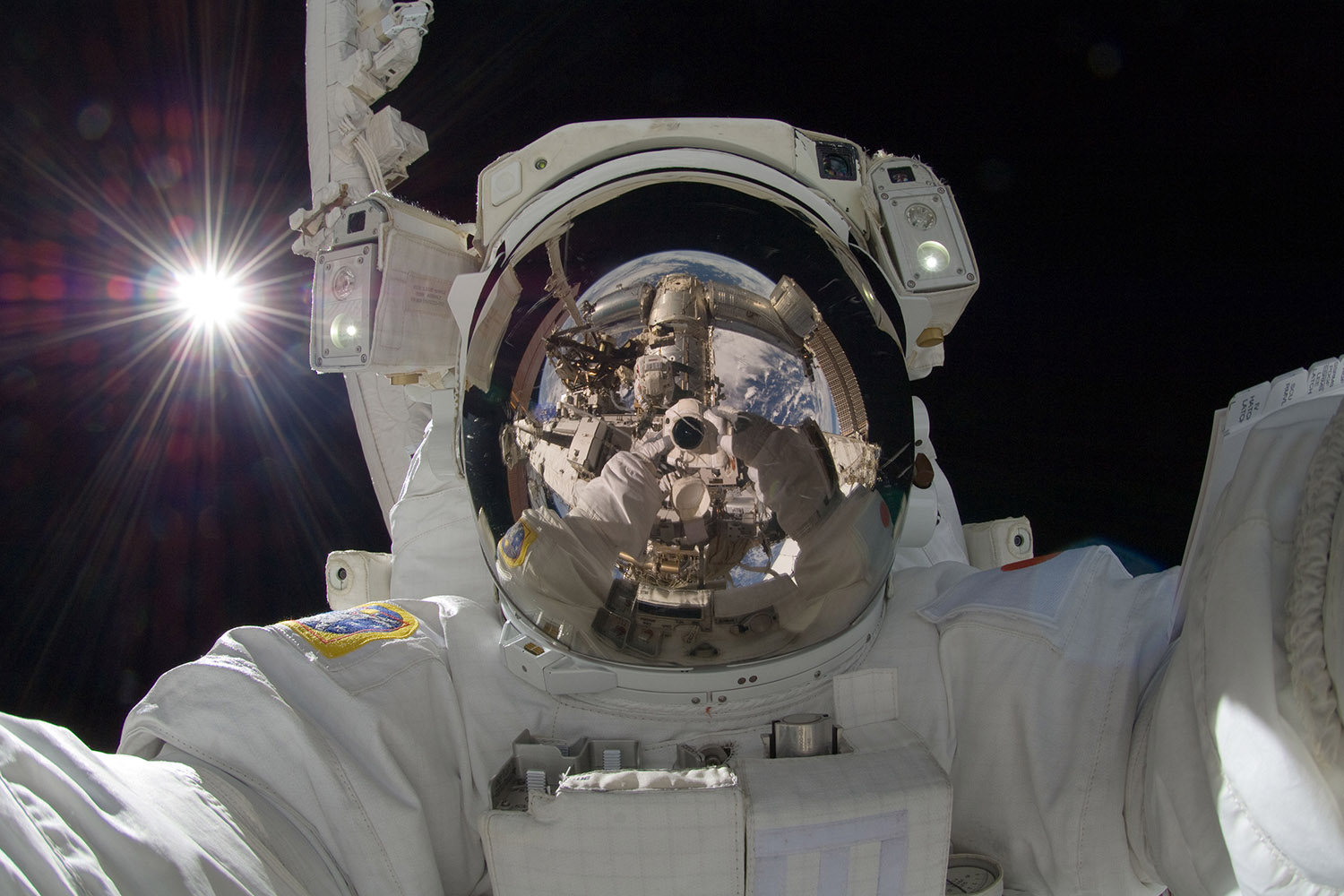Sept. 5, 2012. In this photo provided by NASA, Japan Aerospace Exploration Agency astronaut Aki Hoshide, Expedition 32 flight engineer, uses a digital still camera to take a photo of his helmet visor during the mission's third session of extravehicular activity (EVA).