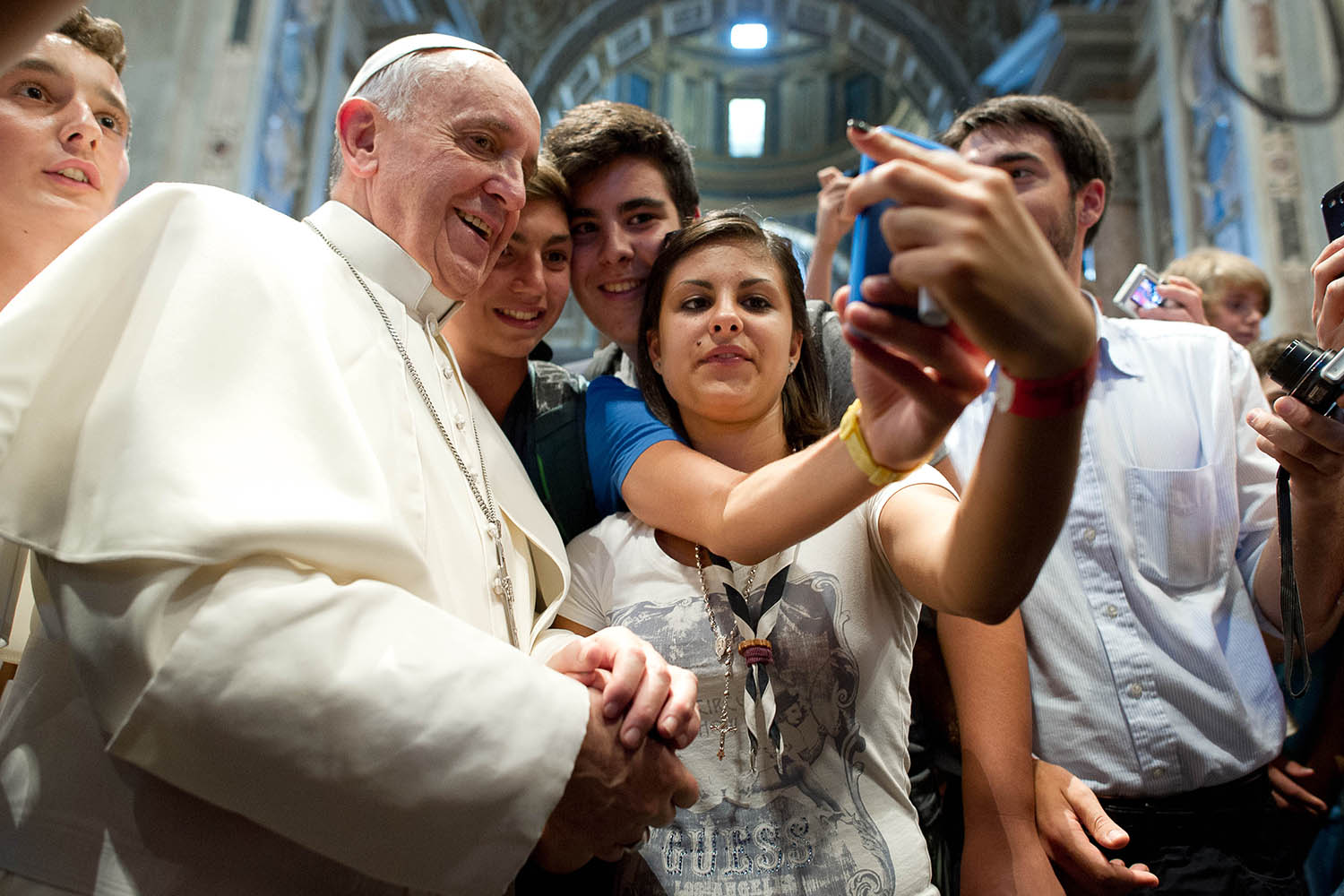 Aug. 28, 2013. In this photo provided by the Vatican newspaper L'Osservatore Romano, Pope Francis has his picture taken inside St. Peter's Basilica with youths from the Italian Diocese of Piacenza and Bobbio who came to Rome for a pilgrimage at the Vatican.