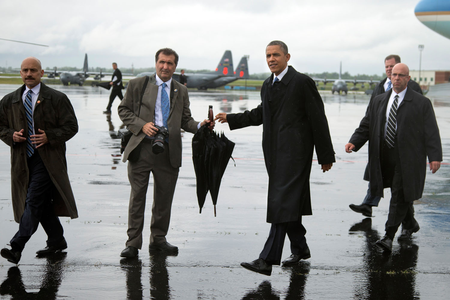 President Obama hands his umbrella to White House photographer Pete Souza before greeting a group of soldiers after arriving at Charlotte-Douglas International Airport in Charlotte, N.C., June 6, 2013.