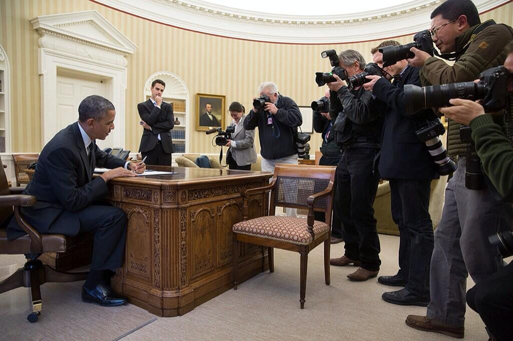 In a photograph released by White House photographer Pete Souza on Twitter, photographers document President Obama signing a bill in the White House November 21, 2013.