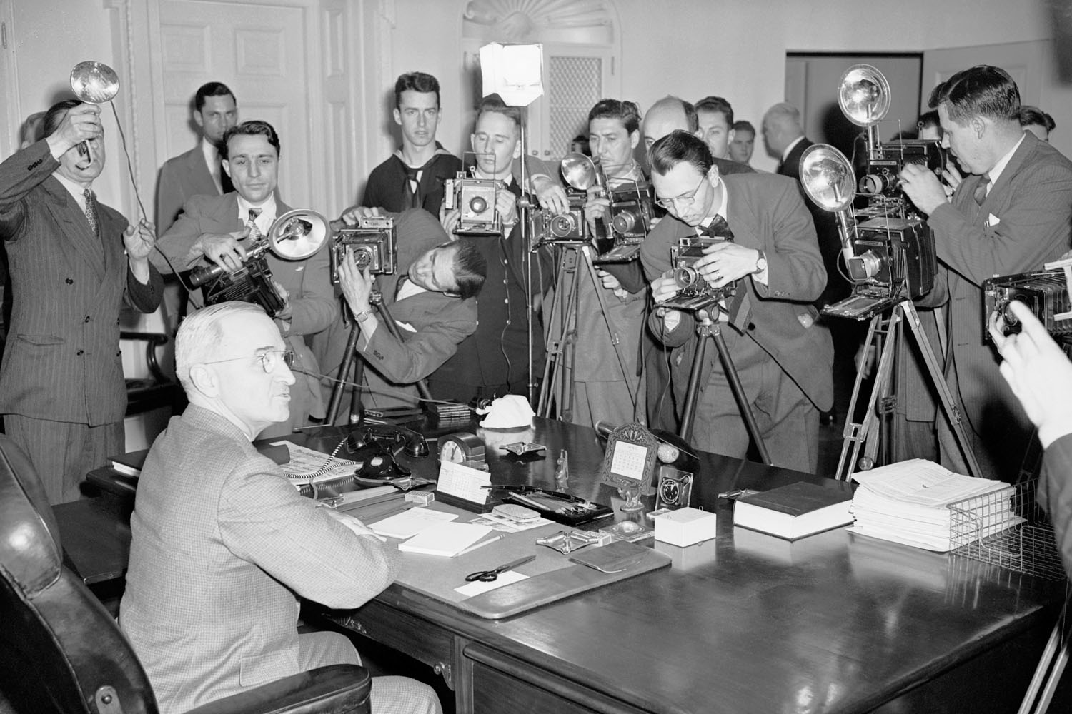 President Harry S. Truman poses at his desk for a group of White House photographers, April 28, 1945.