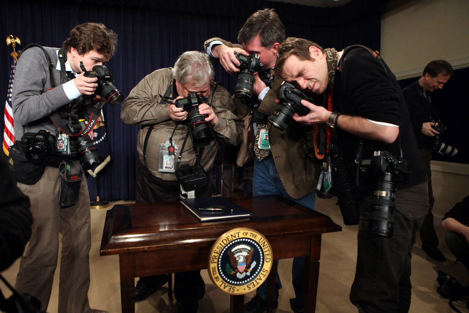 Photographers take pictures of the folio containing an executive order and the president's pen, just before President Obama signed it on January 21, 2009.