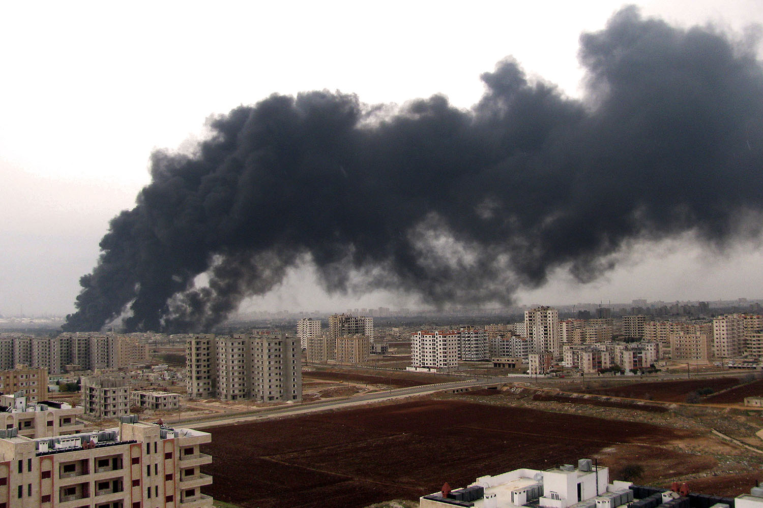 Dec. 8, 2011. A photo released by Syrian news agency SANA shows smoke rising behind residential buildings after the bombing of a pipeline transporting oil to the refinery in Homs, Syria.