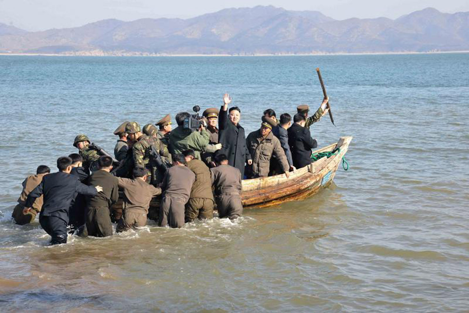 March 11, 2013. In this photo provided by North Korea's official KCNA news agency in Pyongyang, North Korean leader Kim Jong-Un (C) waves while in a boat during his visit to the Wolnae Islet Defense Detachment in the western sector of the front line, which is near Baengnyeong Island of South Korea.
