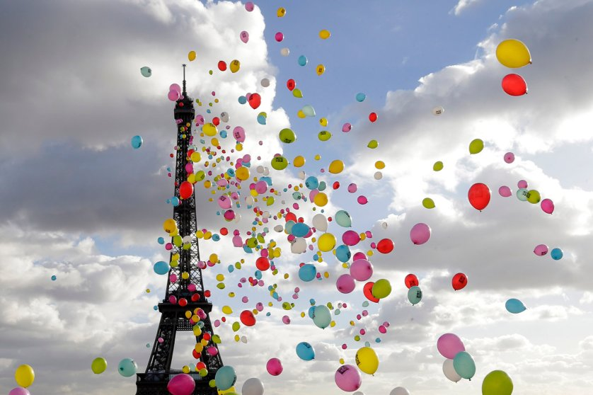 People release a balloons into the air in front of the Eiffel Tower to support four French journalists who are held hostage in Syria