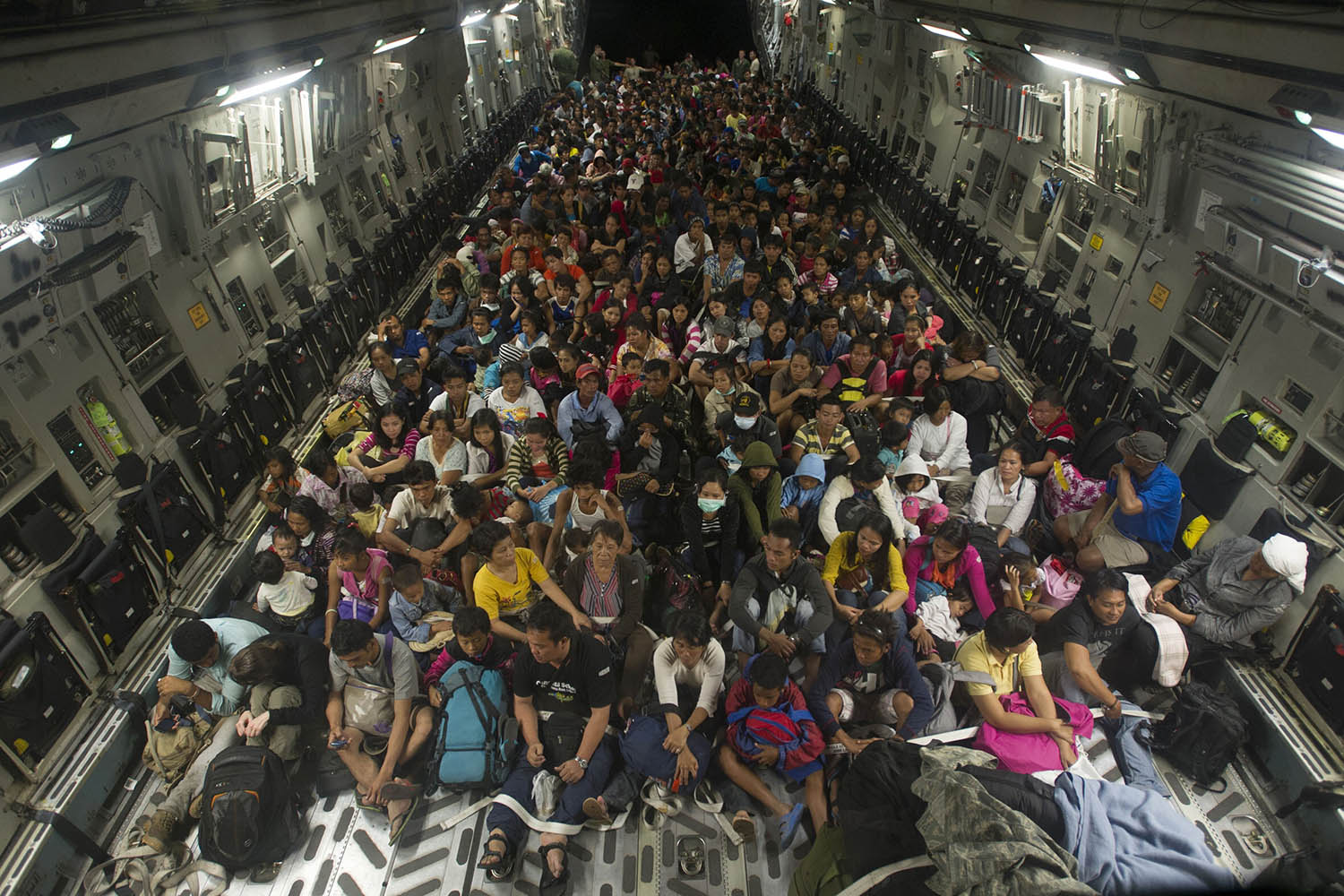 Nov. 22, 2013. This photo released by the U.S. Navy shows Tacloban residents displaced by Typhoon Haiyan fill the cargo hold of a C-17 Globemaster military cargo plane.