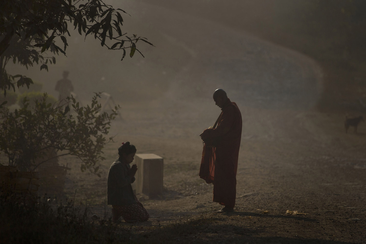 Feb. 21, 2013. A Buddhist devotee prays after offering alms to a Buddhist monk on a street corner near Mong Pan town in central Shan state, Myanmar.
