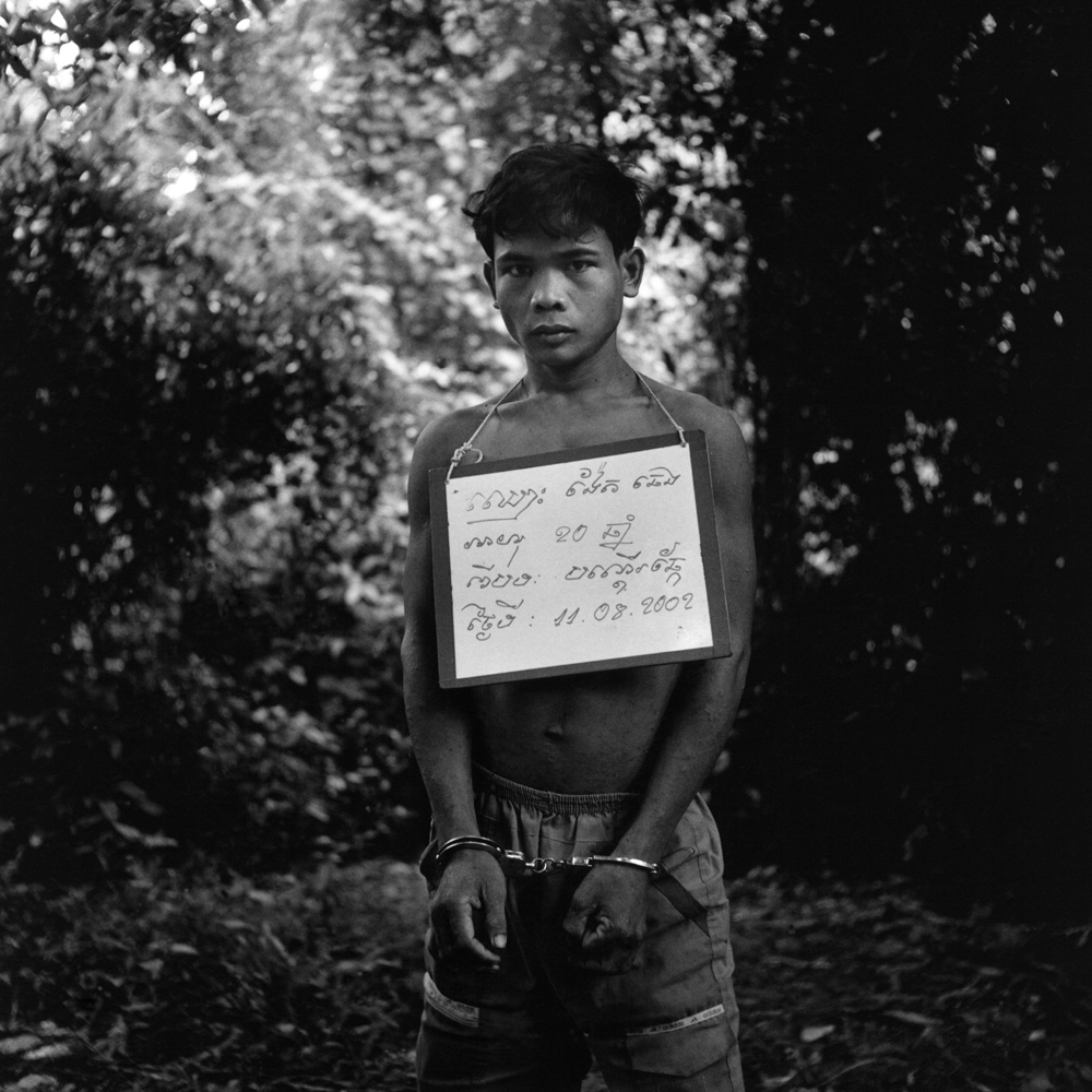 Bokor, Cambodia                                                                                             A handcuffed poacher is photographed with a notice bearing details of his name, age and the nature and date of his crime. While operating as part of a poaching team in Bokor National Park, he was brought for questioning by members of the National Cambodian Forestry Security service.