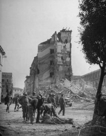 In ruined Anzio American and British soldiers gather around man who has just been hit by fragments of a shell bursting in the street. Casualty had come ashore from the harbor 40 seconds before.