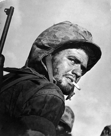 A U.S. Marine peers over his shoulder during the final days of fighting to wrest the island of Saipan from Japanese troops, 1944.