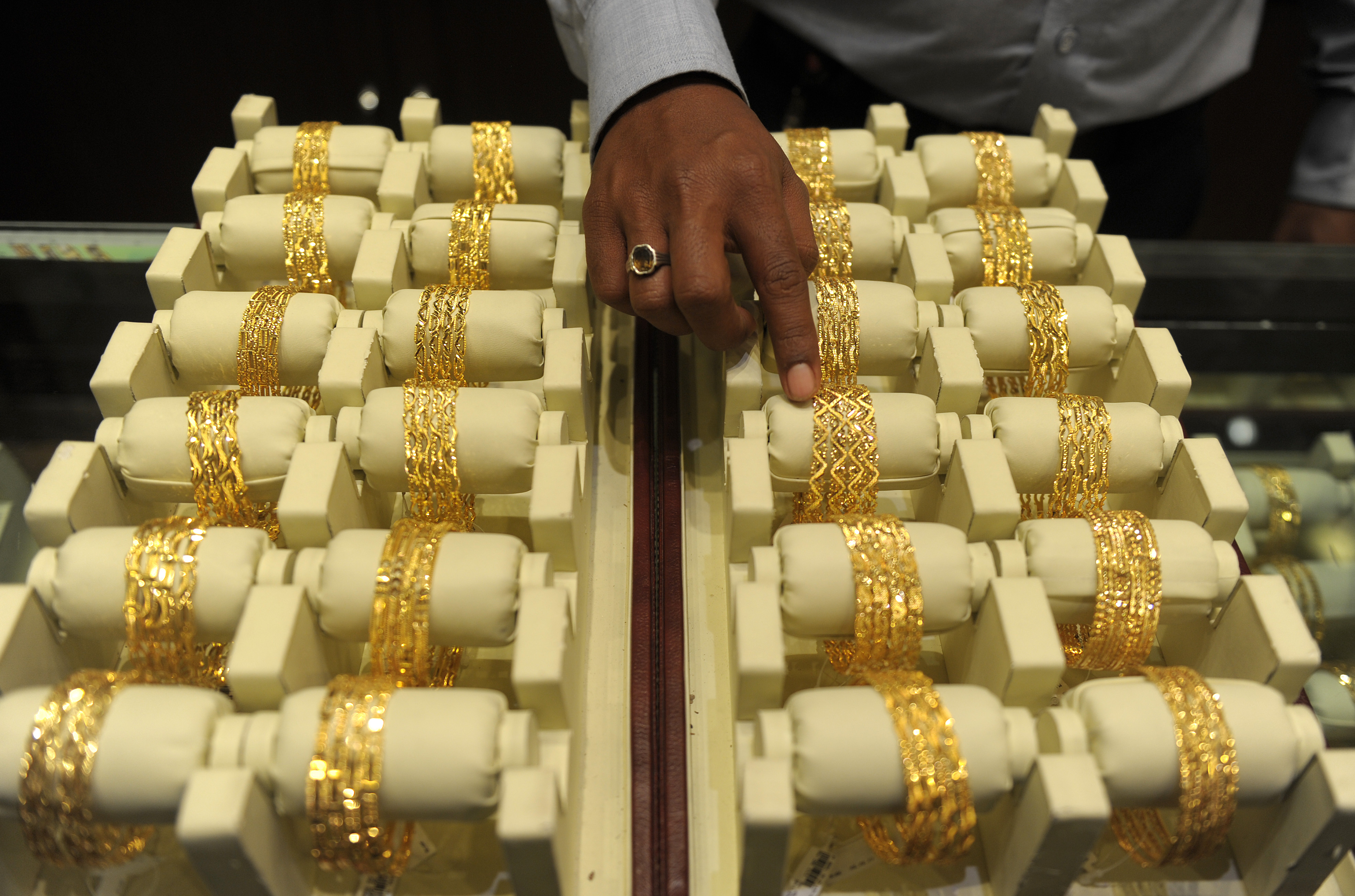 An Indian sales assistant arranges gold bangles in a jewelry shop in Hyderabad, India, on May 13, 2013