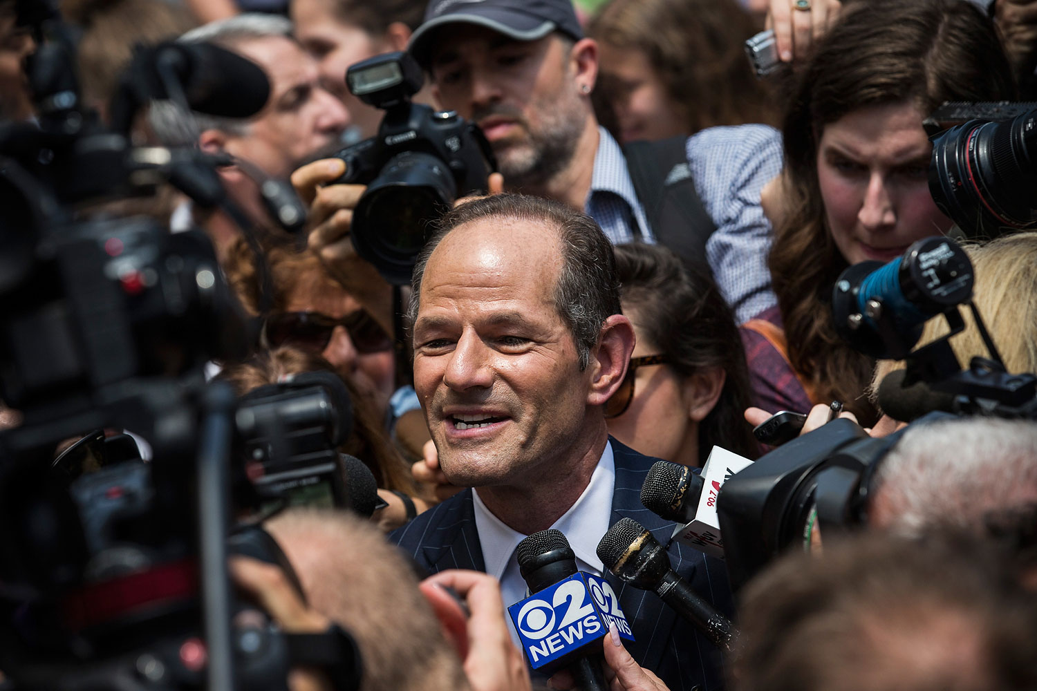 Former New York governor Eliot Spitzer is mobbed by reporters while attempting to collect signatures to run for comptroller of New York City on July 8, 2013, in New York City