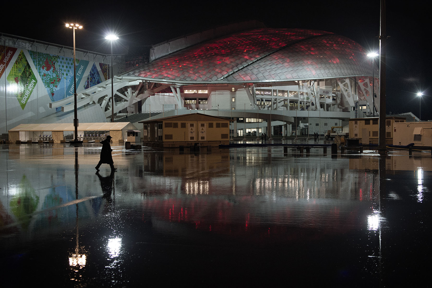 Jan. 17 2014. A security guard walks passed the newly built Fisht Stadium during a midnight rehearsal for the opening ceremony of the Winter Olympics in Sochi.