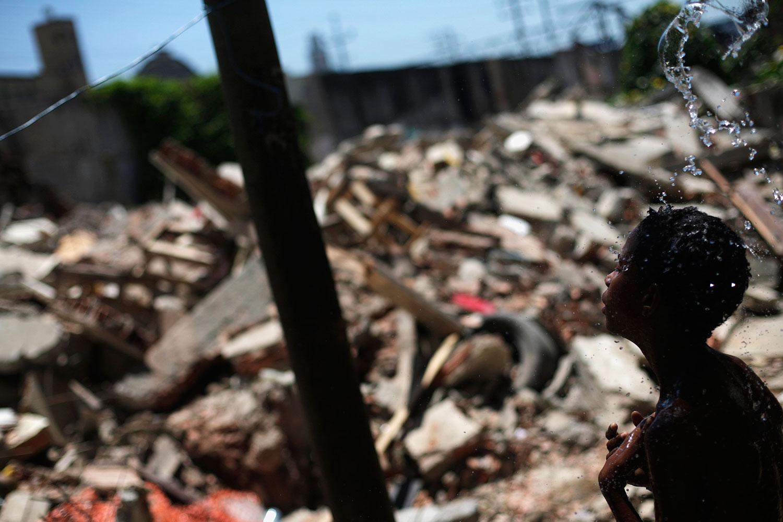 Jan. 9, 2014. A boy takes a shower at a demolished area in Metro slum, near Maracana stadium, in Rio de Janeiro.