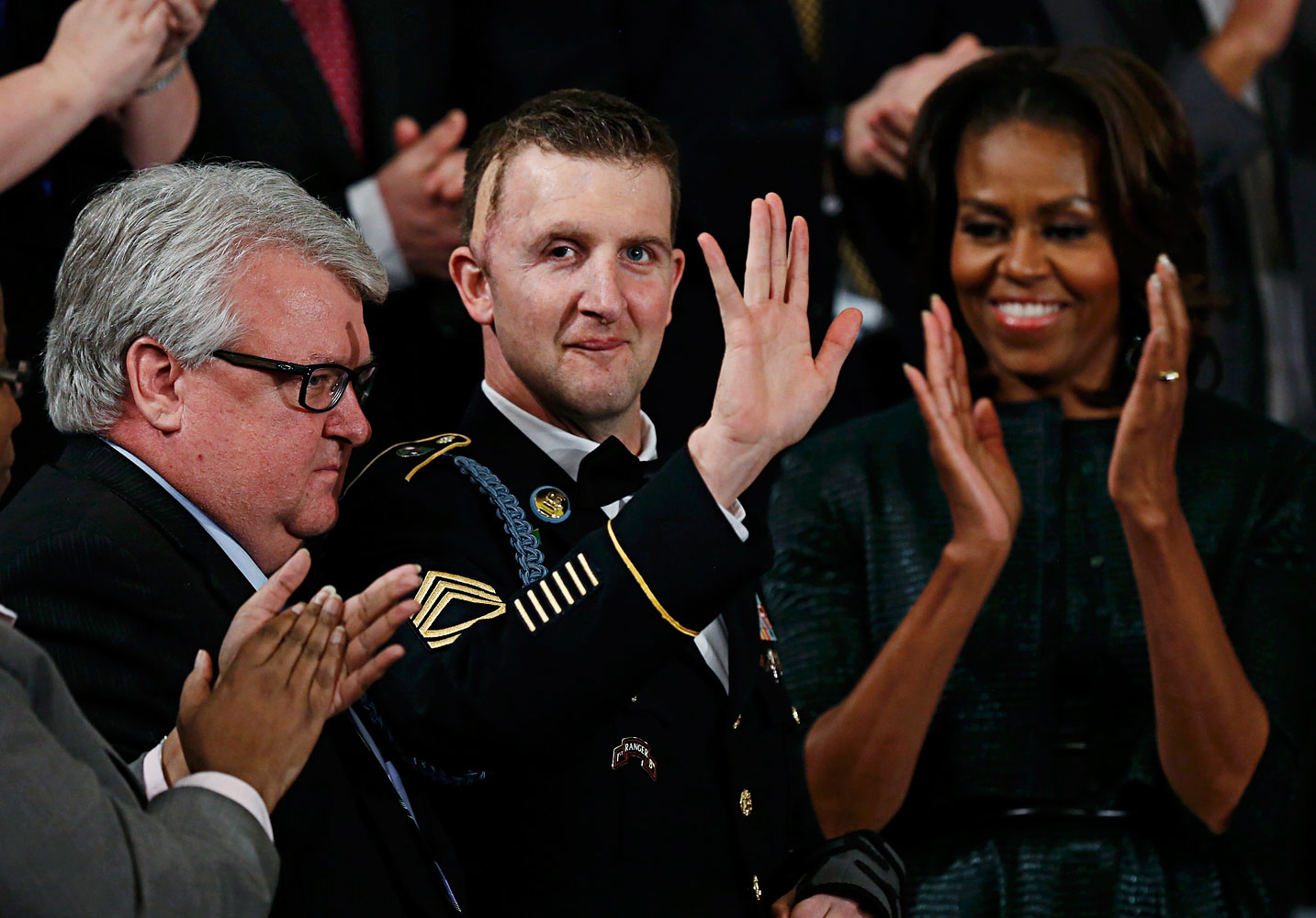 First lady Michelle Obama applauds U.S. Army Ranger Sgt. First Class Cory Remsburg, injured while serving in Afghanistan, during President Barack Obama's State of the Union speech on Capitol Hill in Washington, Jan. 28, 2014.