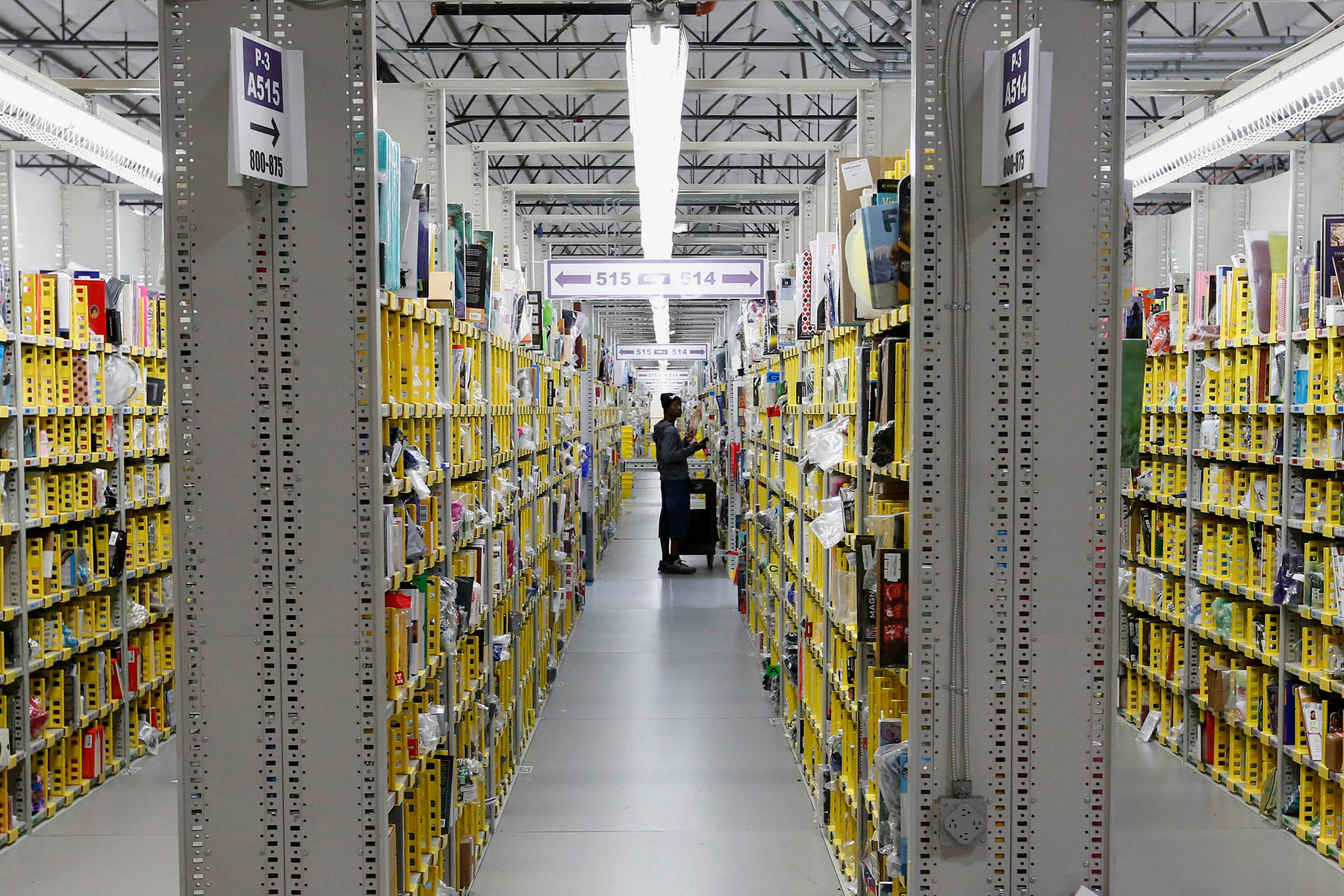 An Amazon.com employee stocks a shelf at an Amazon.com Fulfillment Center