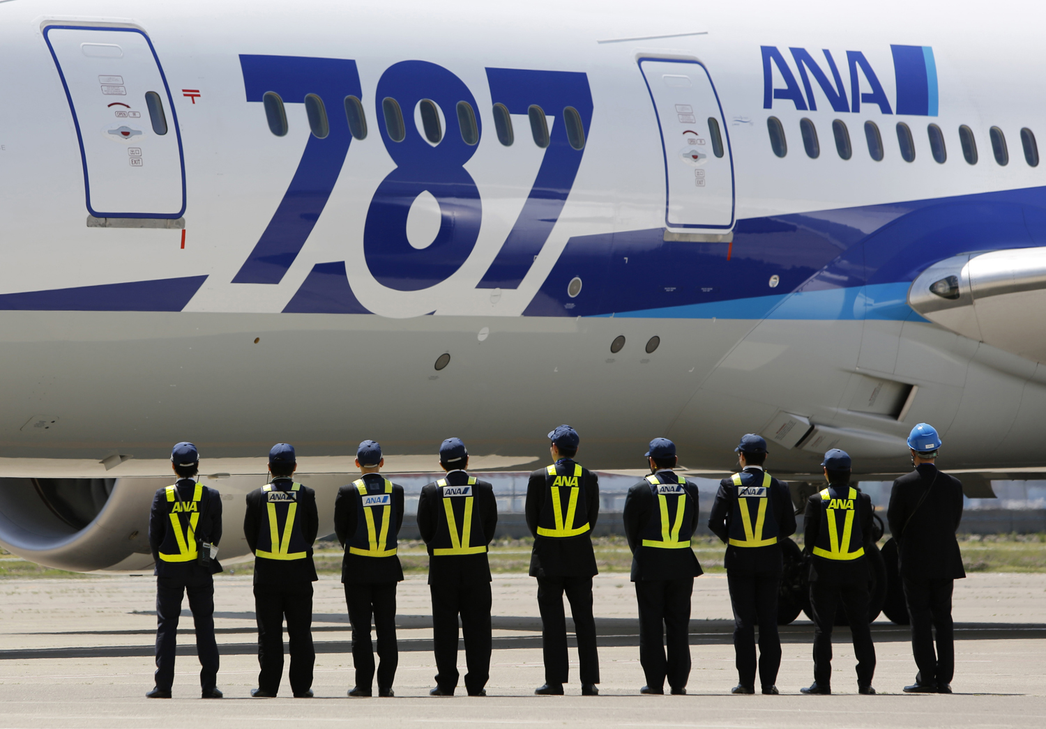 All Nippon Airways' employees stand in front of the company's Boeing 787 Dreamliner plane after it's test flight at Haneda airport in Tokyo on April 28, 2013