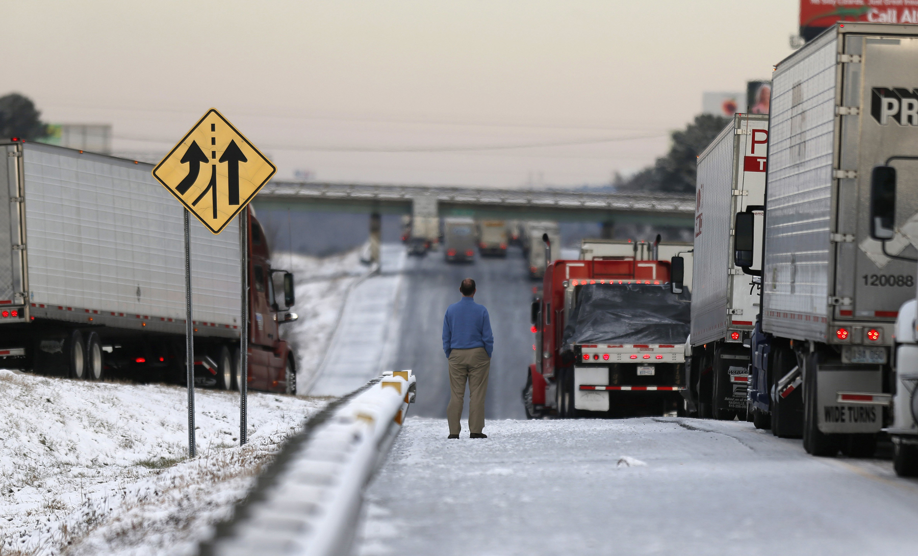 A man stands on the frozen roadway as he waits for traffic to clear along Interstate 75 Wednesday, Jan. 29, 2014, in Macon, Ga.