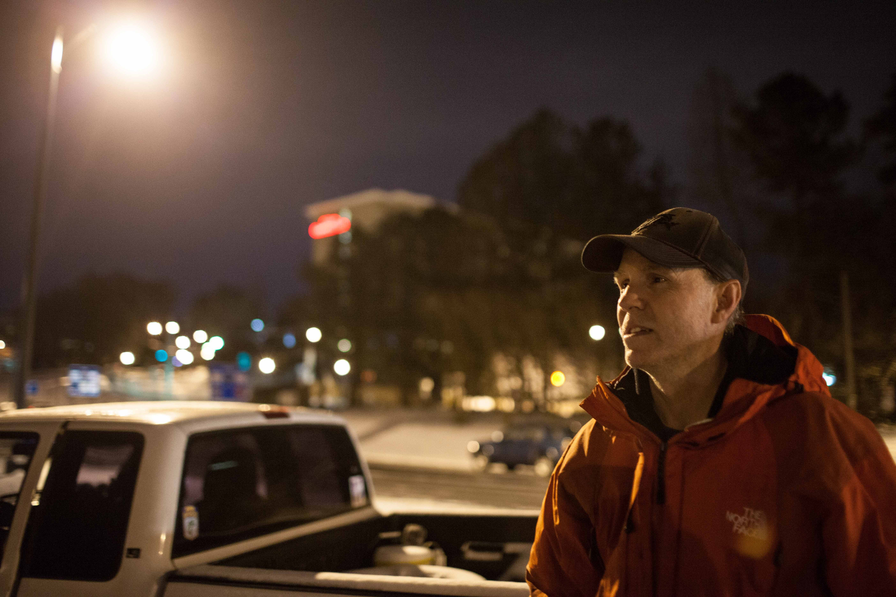 Jeff Brown stands outside of his truck that he slept in Tuesday night after being stranded on Interstate 285, early Wednesday, Jan. 29, 2014, in Dunwoody, Ga.
