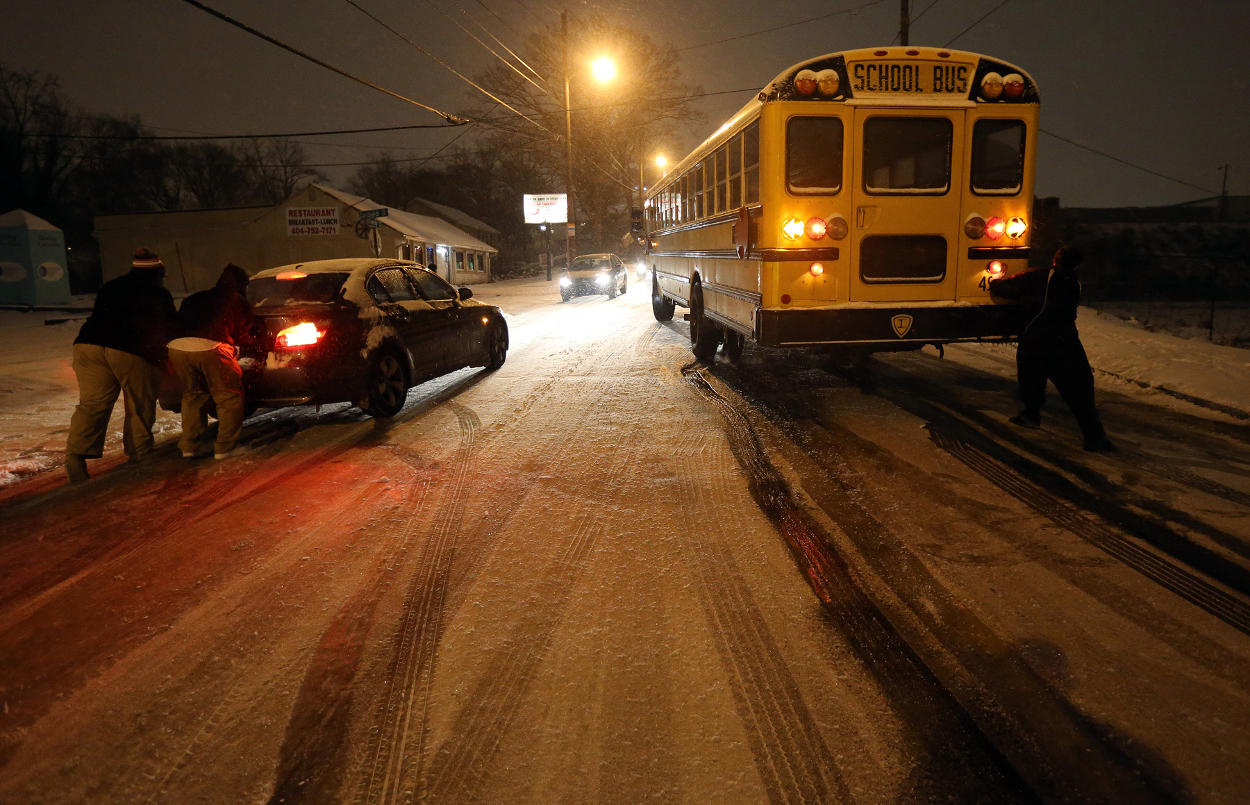 People work to push a stuck Atlanta school bus and a car on an icy stretch of University Avenue in Southwest Atlanta on Tuesday, Jan. 28, 2014. The bus was eventually moved off the road and left for the night.