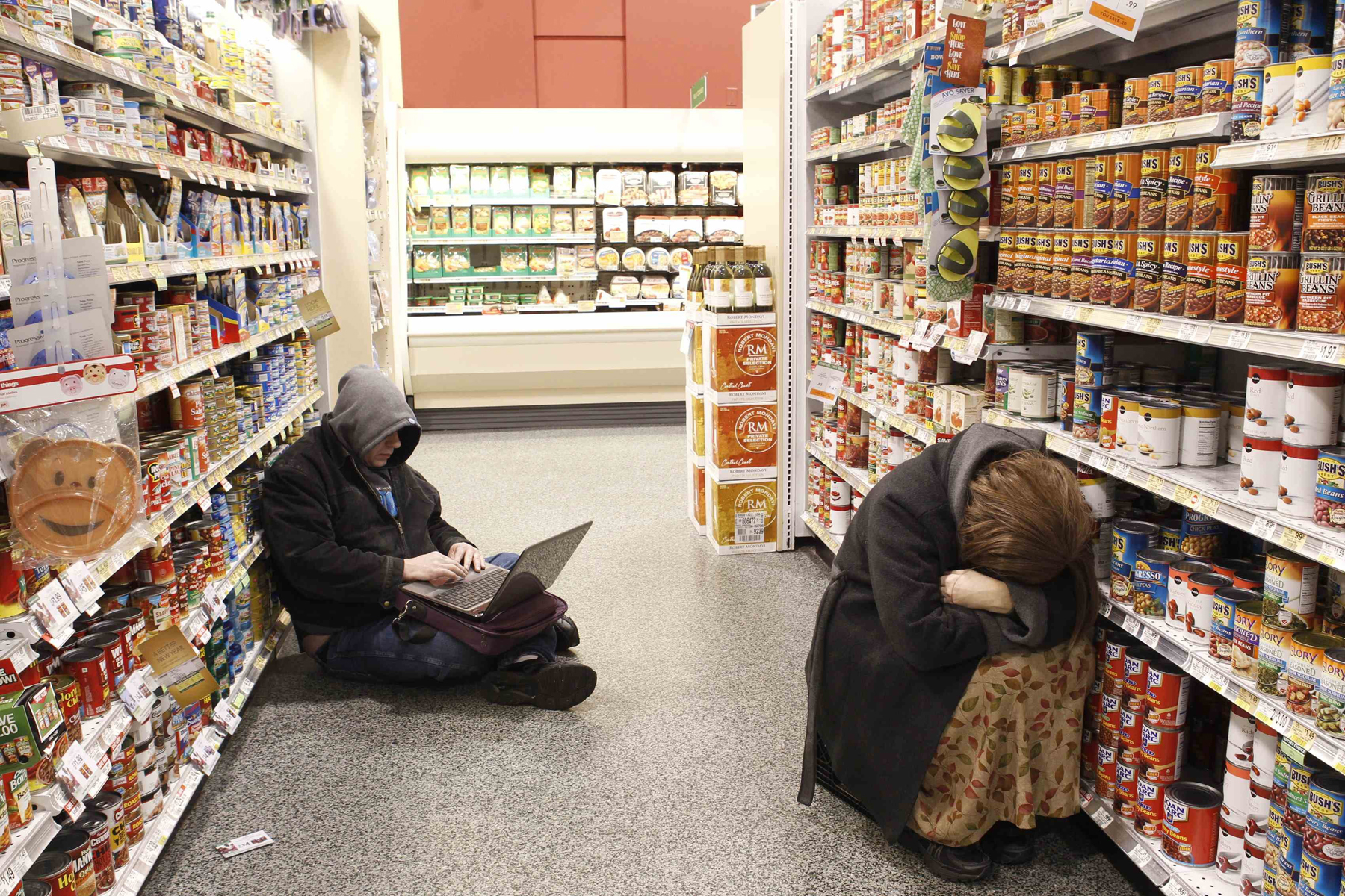 People rest at aisle of a Publix grocery store after being stranded due to a snow storm in Atlanta