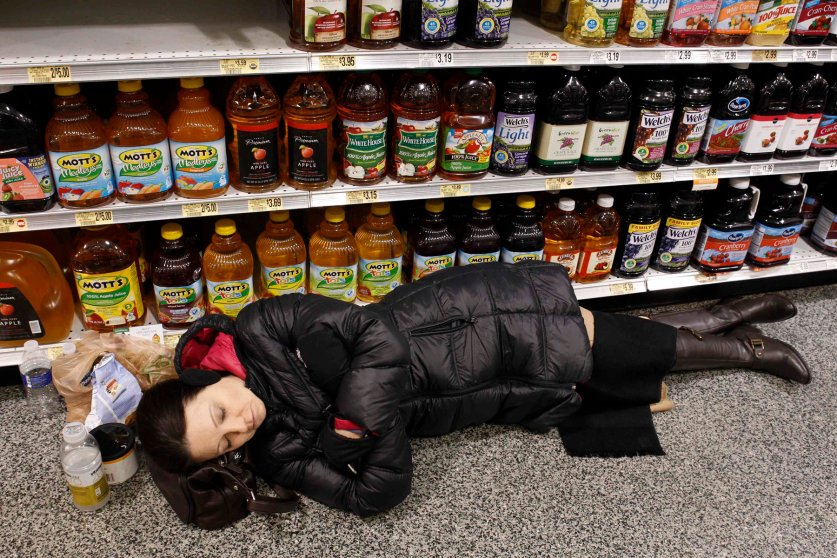 Karen Wang sleeps at the aisle of a Publix grocery store after being stranded due to a snow storm in Atlanta, Jan. 29, 2014.