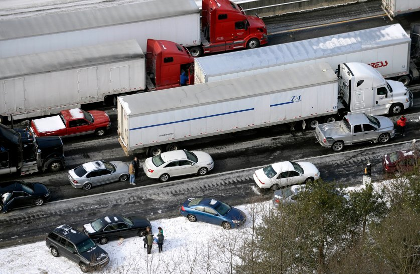 Motorists get out of their vehicles to chat near abandoned cars along the ice-covered I-75 north at Moors Mill Rd., Jan. 29, 2014, in Atlanta.