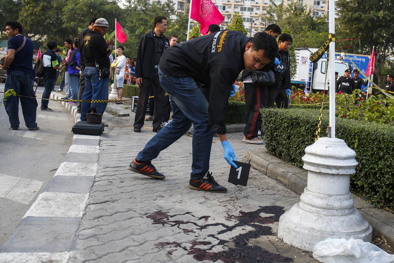 A forensic police officer drops a marker next to blood at the site of what police say were clashes between anti-government protesters and supporters of Prime Minister Yingluck Shinawatra in Bangkok January 26, 2014