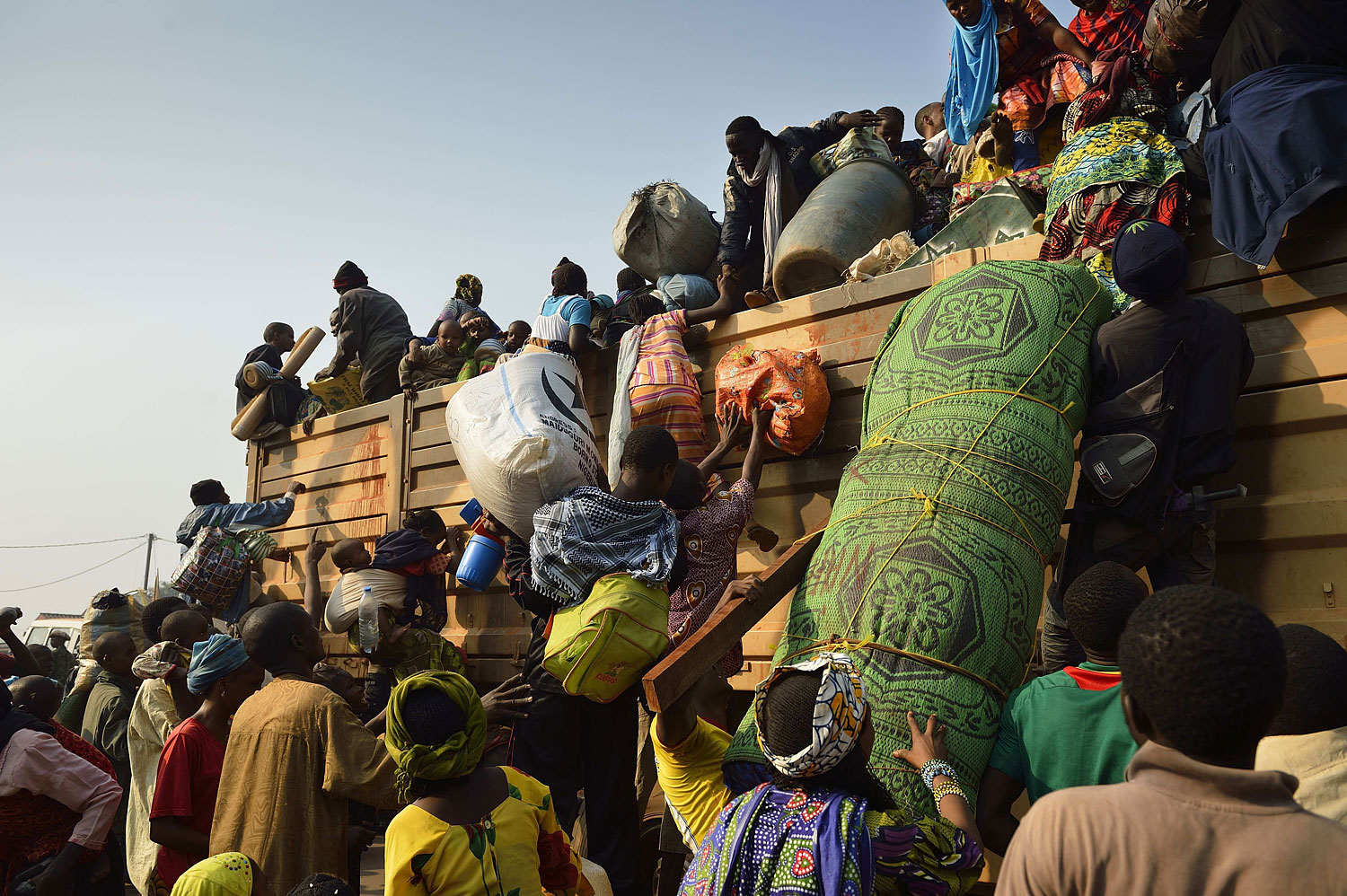 Chadian civilians climb on a military chadian truck to go back to Chad on Jan. 15, 2014, in the PK12 district of Bangui.
