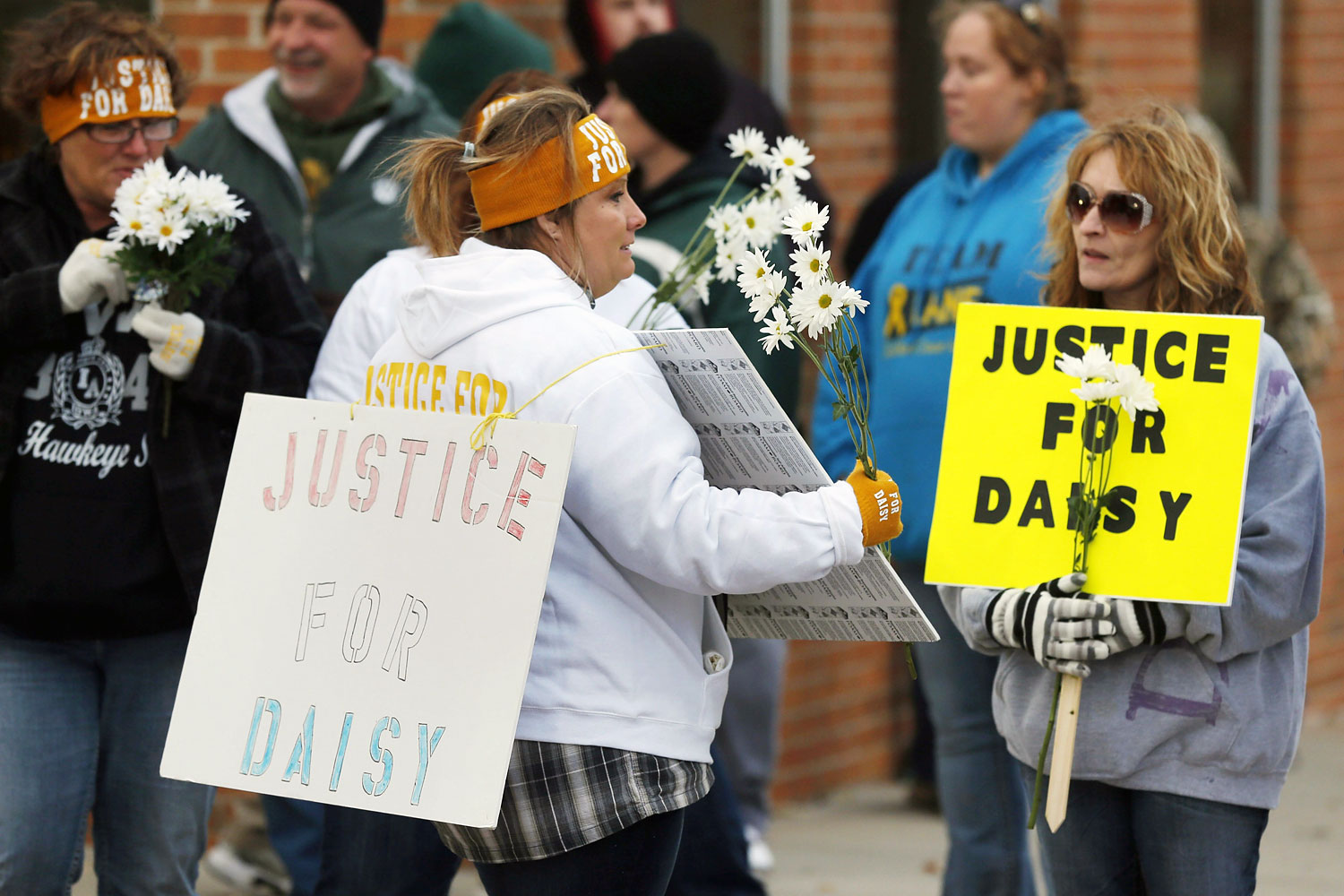 Supporters pass out flowers in Maryville, Mo., before a rally for Daisy Coleman, Oct. 22, 2013.