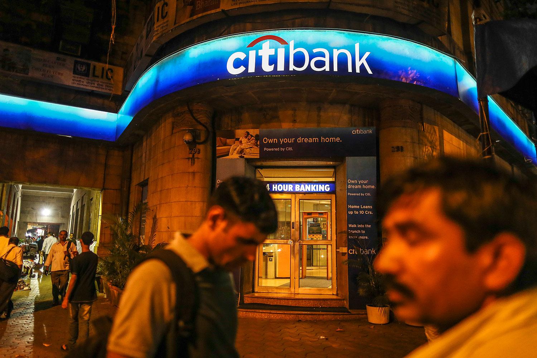 Pedestrians walk past a Citibank branch in Mumbai