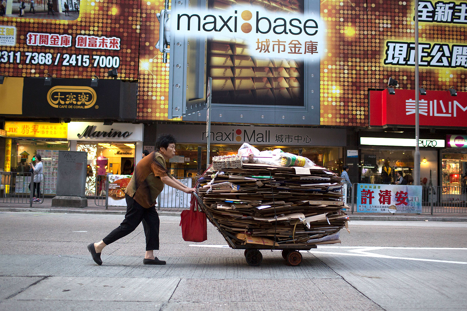 An elderly woman pushes a cart filled with cardboard for recycling in the North Point area of Hong Kong, China, on Oct. 18, 2013