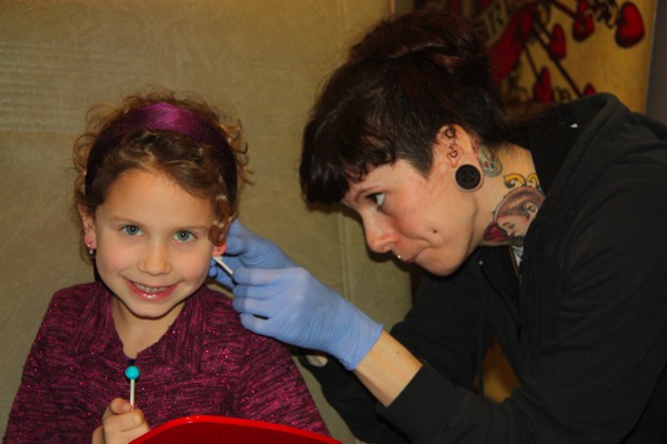Sarah LaRoe pierces my daughter's ears at Pierced Hearts, a Seattle tattoo parlor.