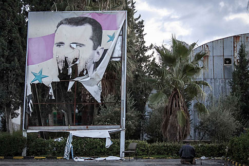 A Free Syrian Army fighter offers evening prayers beside a damaged poster of Syria's President Bashar Assad during heavy clashes with government forces in Aleppo, Syria, on Dec. 8, 2012.