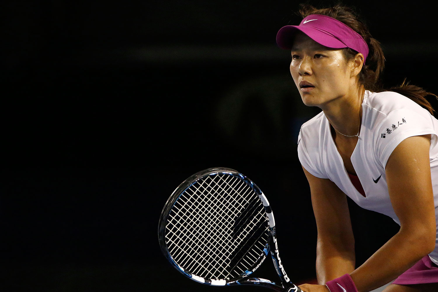 Li Na of China prepares to receive a serve from Dominika Cibulkova of Slovakia during their women's singles final match at the Australian Open 2014 tennis tournament in Melbourne Jan. 25, 2014