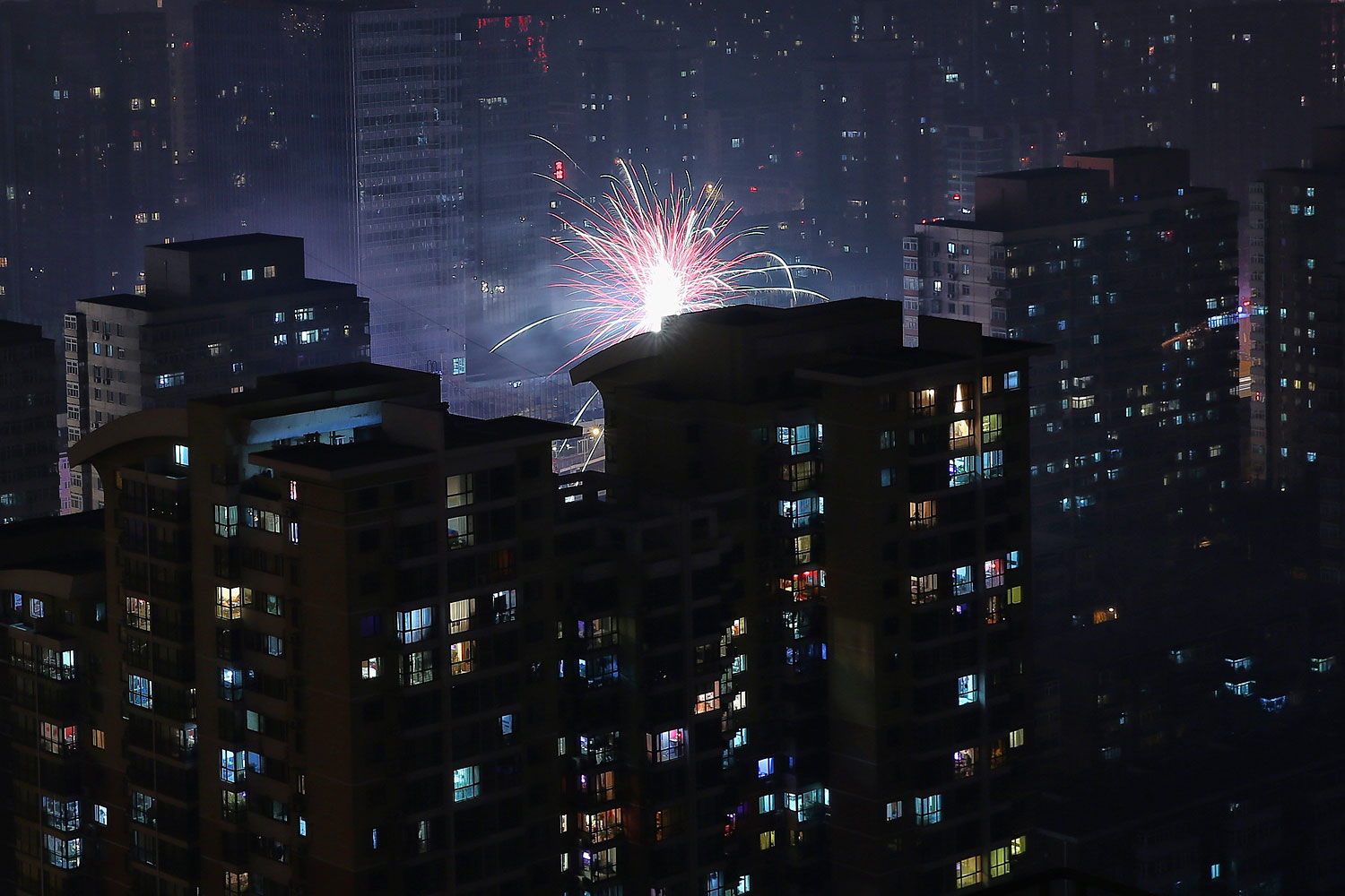 Fireworks illuminate a residential area to celebrate Chinese Lunar New Year of Horse and cause severe air pollution on Jan. 30, 2014 in Beijing.