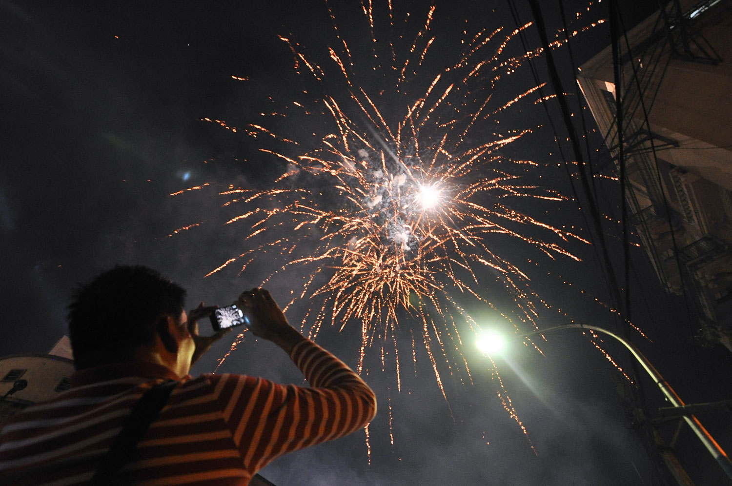 A man films the fireworks display using his phone in Chinatown, on the eve of Chinese New Year in Manila, Philippines,  Jan. 30, 2014.