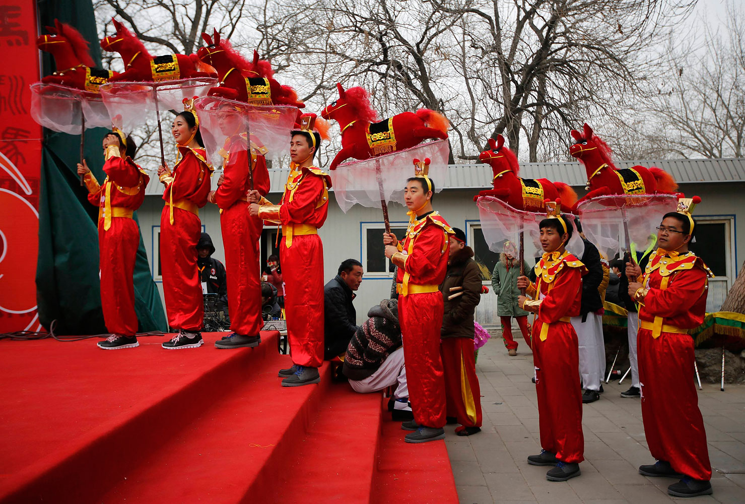 Folk dancers hold horse models as they prepare to take part in a traditional horse dance on the first day of the Chinese Lunar New Year, which welcomes the Year of the Horse, at the Longtan park in Beijing Jan. 31, 2014.