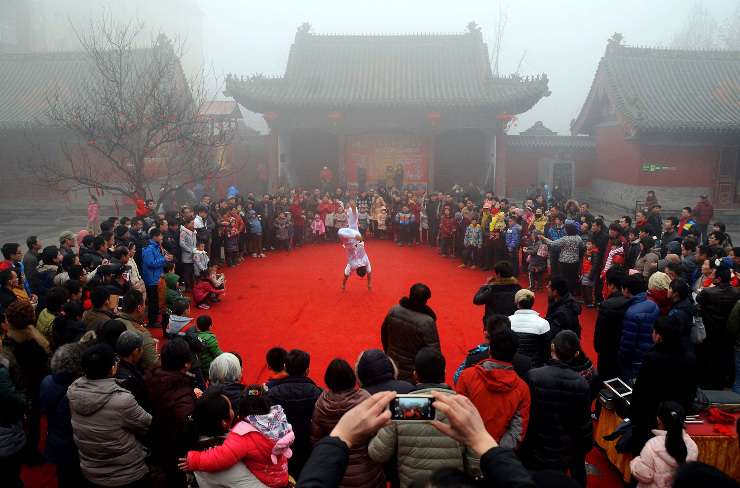 Visitors view a performance at a temple fair celebrating the Lunar New Year, known as the Spring Festival, in Zhengzhou, capital of Central China's Henan Province, Jan. 31, 2014.