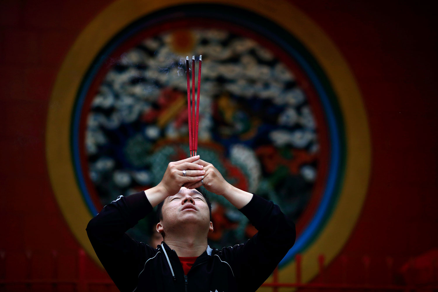 A man prays for good fortune while holding incense on the first day of the Chinese Lunar New Year at Petak Sembilan Temple, in Jakarta, Jan. 31, 2014.