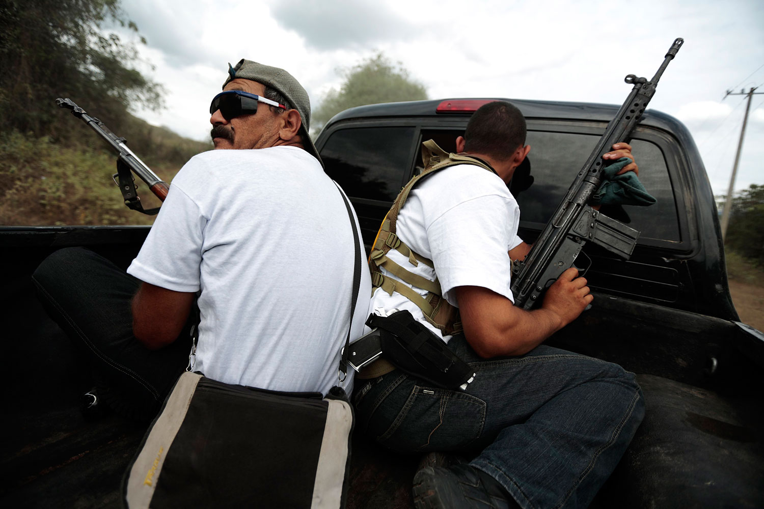Vigilantes ride on the back of a pick-up truck while driving in a convoy to Poturo, Michoacan, Dec. 29, 2013.