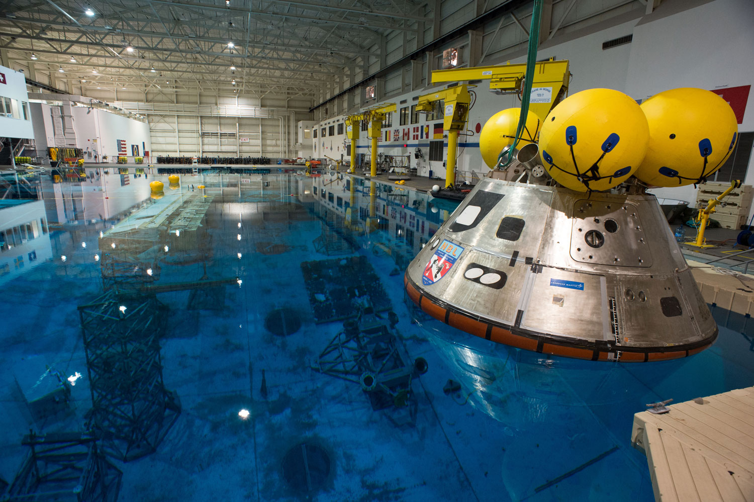 A model of Orion floats above an underwater mockup of the International Space Station in the 40-foot (12 m) deep Neutral Buoyancy Laboratory in Houston on April 25, 2013. The model is used to practice splashdown operations for Orion's first flight test in 2014. The yellow balls on the top of the capsule are flotation balloons which would flip the vehicle into the proper orientation if it were to turn upside down after landing.