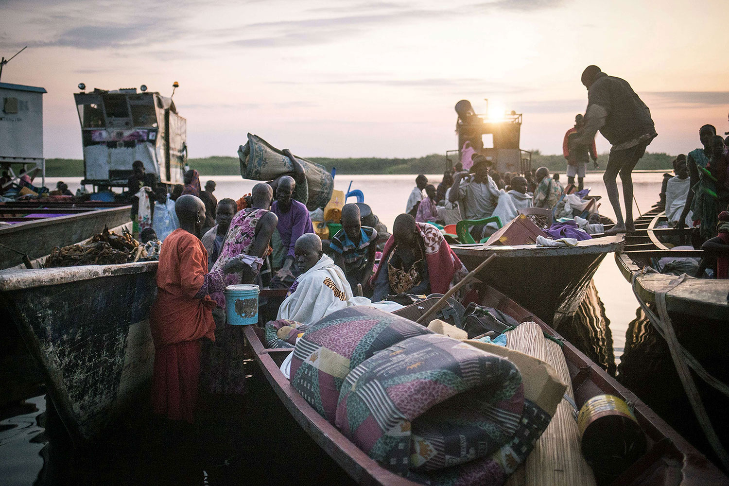 Jan. 9, 2014. People unload their few belongings that they were able to bring with them to refugee camps, Minkammen, South Sudan
