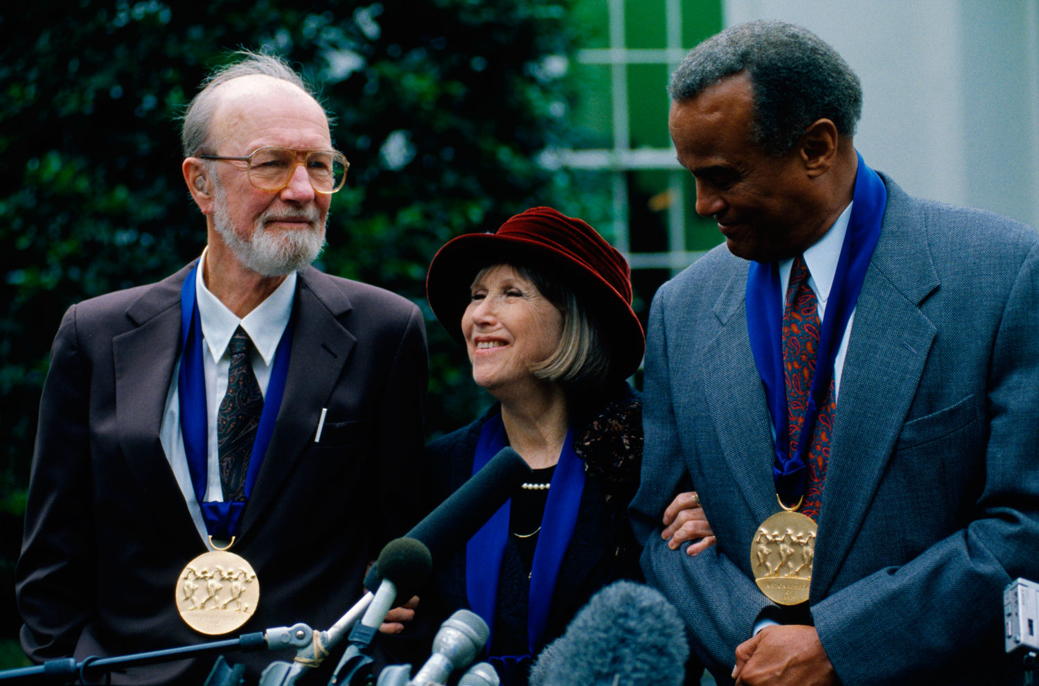 From left: Pete Seeger, actress Julie Harris, and actor Harry Belafonte speak at a press conference after being awarded the National Medal of Arts by President Clinton in Washington, D.C., on Oct. 14, 1994.