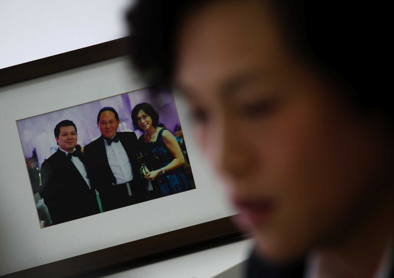 Gigi Chao, the daughter of Hong Kong property tycoon Cecil Chao, next to a family photo of herself; her father, center; and brother Howard at her office in Hong Kong on Sept. 27, 2012